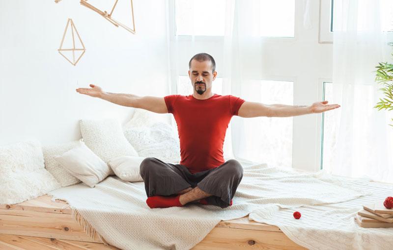 ベッドの上であぐらを組み両腕を大きく広げている男性