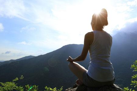 山に向かって安楽座で座る女性