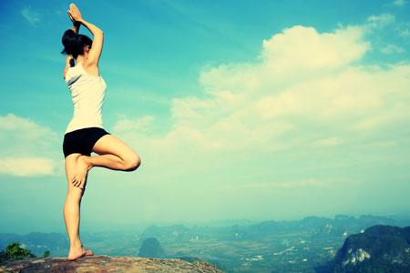 頂上で木のポーズをする女性