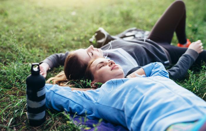 スポーツウェアを着た女性が2人芝生の上で寝転んでいる