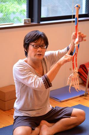 腕の骨模型を持つ内田かつのり先生
