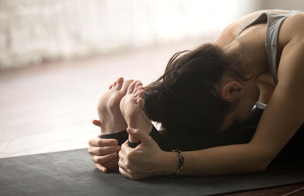 黒いヨガマットの上で、前屈して足を抱えたポーズをとる女性の写真