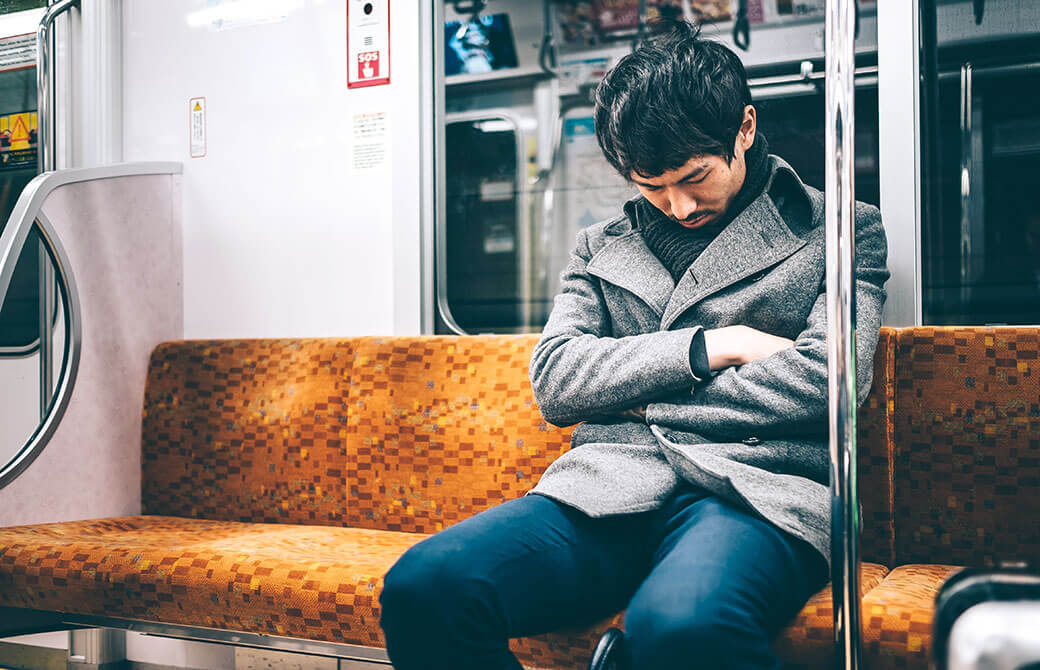 電車の中で居眠りするコートを羽織った男性の写真