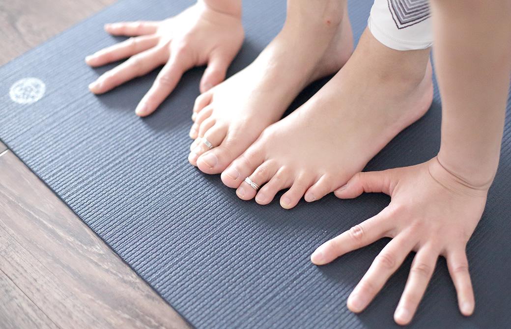 黒色のヨガマットの上で両手足をマットにつけている写真