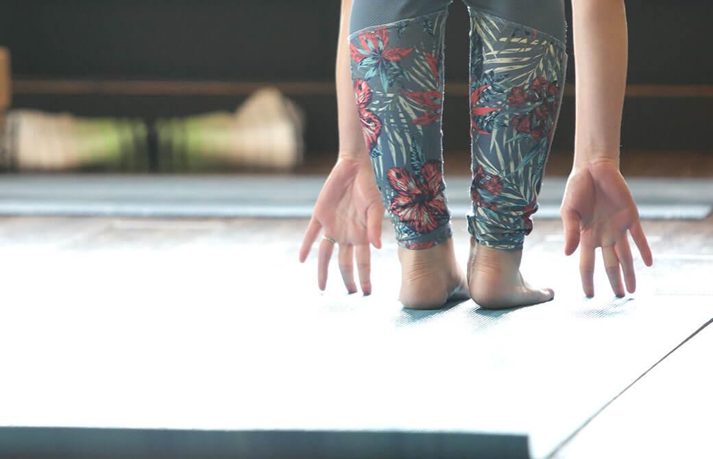 ヨガマットの上で女性が前屈をしている画像