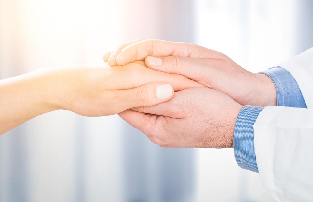 男性が女性の手を握っている