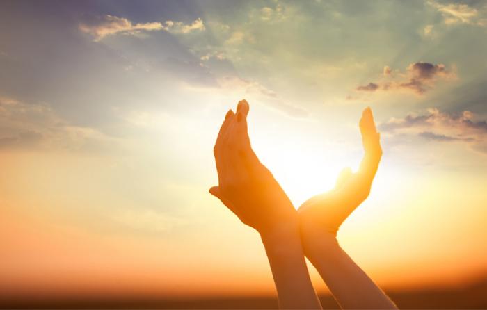 太陽に両手をあてている