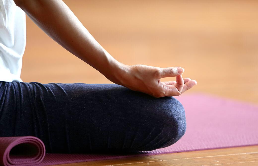床の上に敷いたピンクの待ったの上であぐらをかいて瞑想をしている人の脚と手の写真