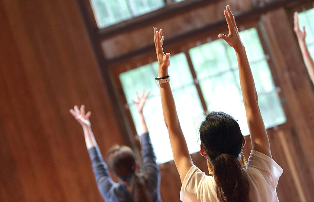 体育館でヨガクラスをしていて、生徒さんが両手を挙げている写真
