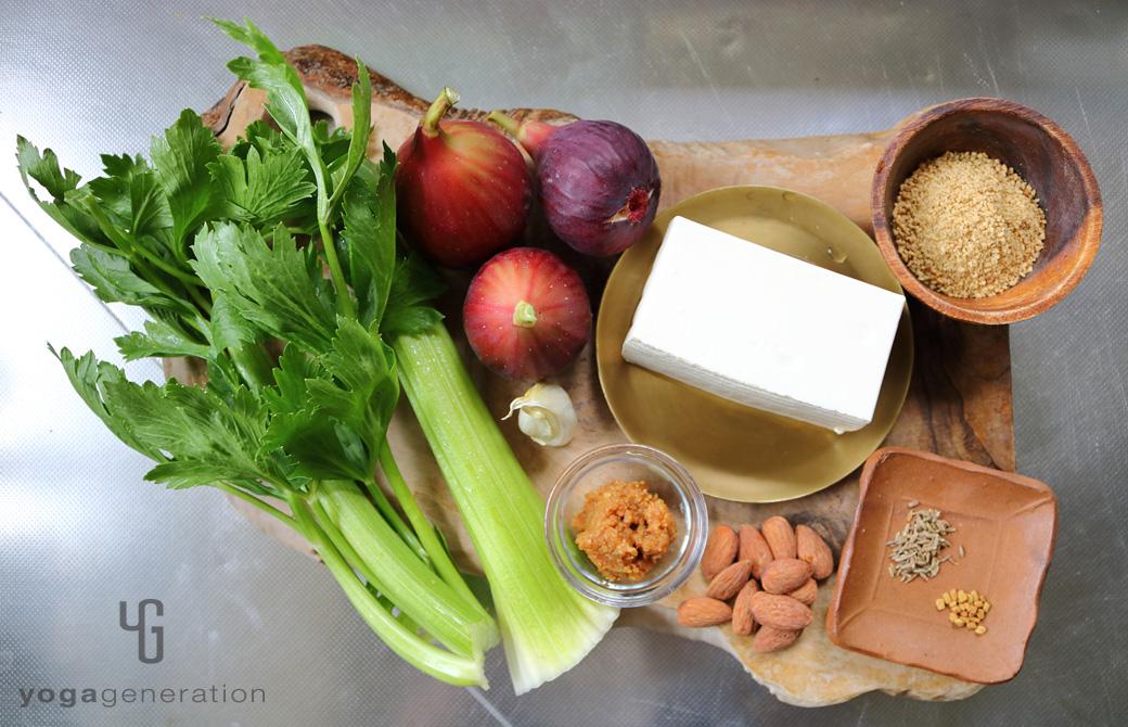 木製カットボードの上のイチジクやセロリ、豆腐などの材料