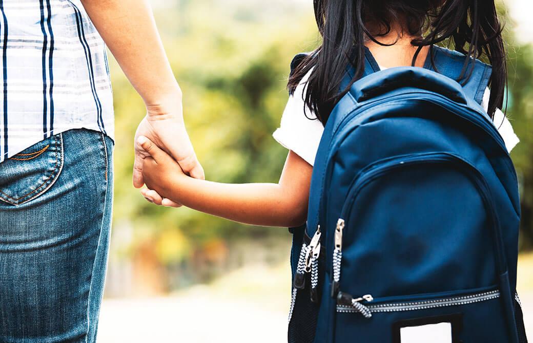 リュックを背負った女の子と手を繋いだ親