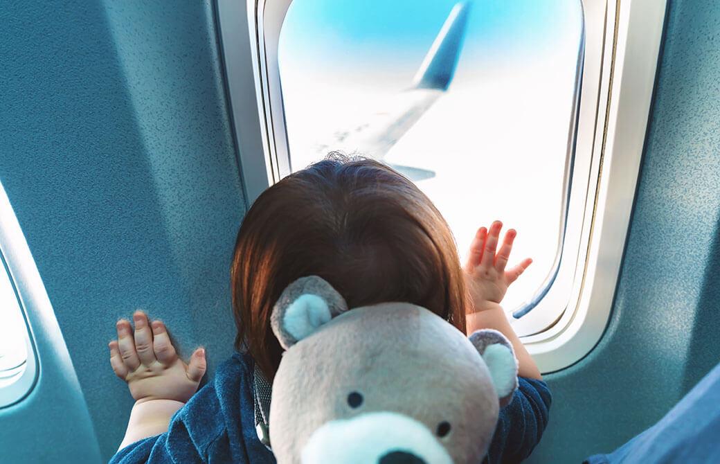 飛行機の窓から外を見る子ども
