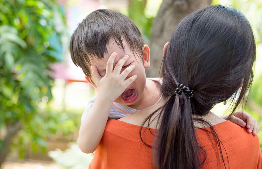 お母さんに抱っこされて泣いている子ども