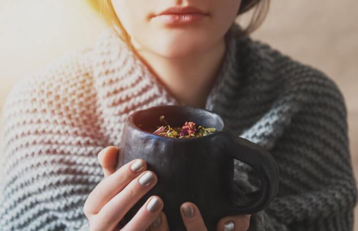 ハーブティーのカップを両手で持った女性