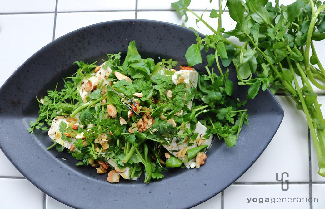 黒色の皿に盛りつけたガーリック・レモンドレッシングでクレソンとお豆腐のサラダ