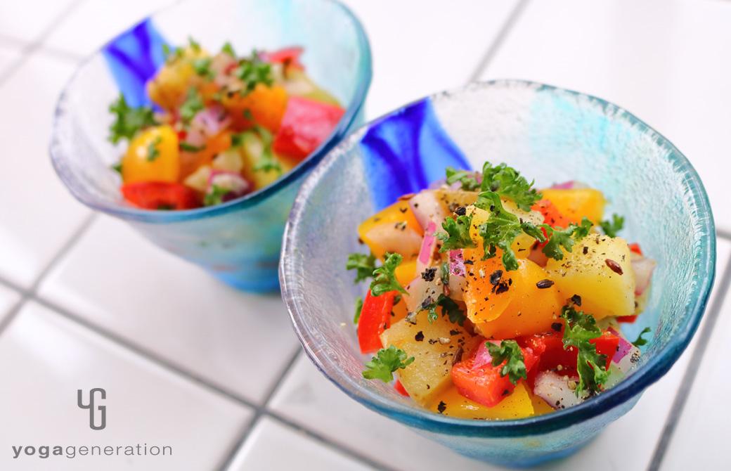 ガラス製のターコイズブルーの器に盛りつけたビタミンカラーの揚げじゃがサラダ