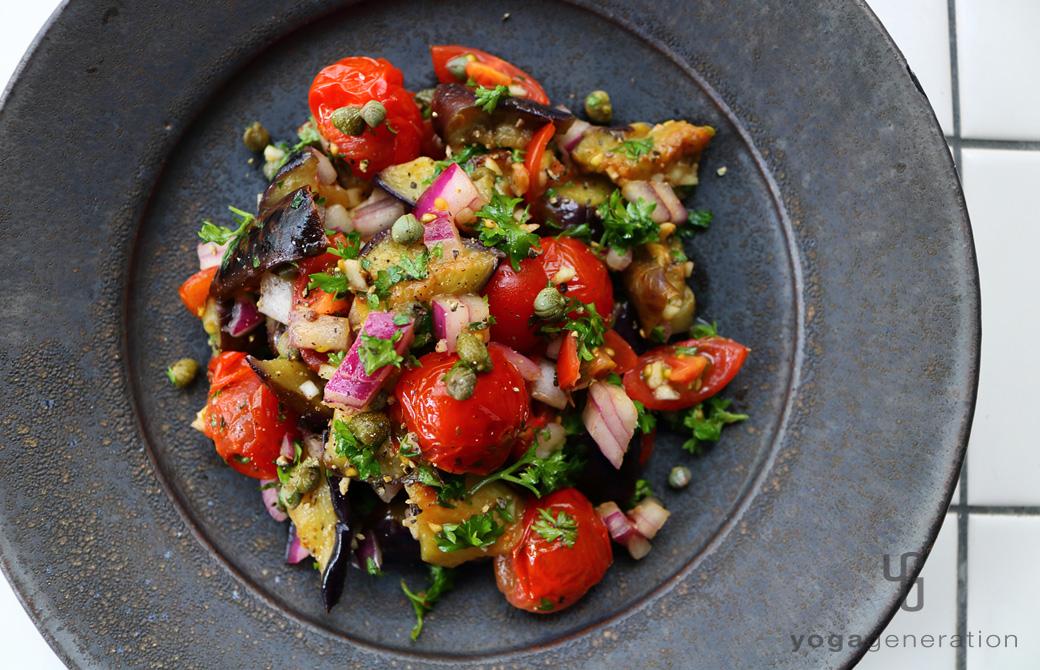 黒い皿に盛りつけたケイパーを効かせたナスとトマトのマリネ