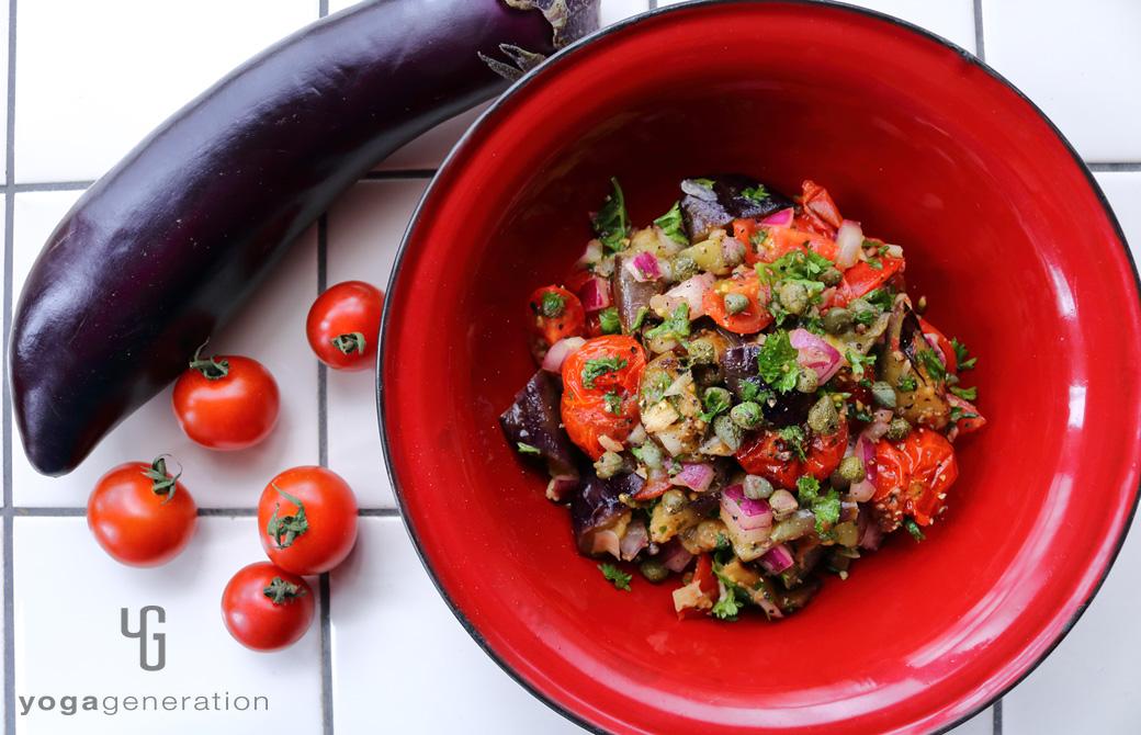 赤の皿に盛りつけたケイパーを効かせたナスとトマトのマリネ