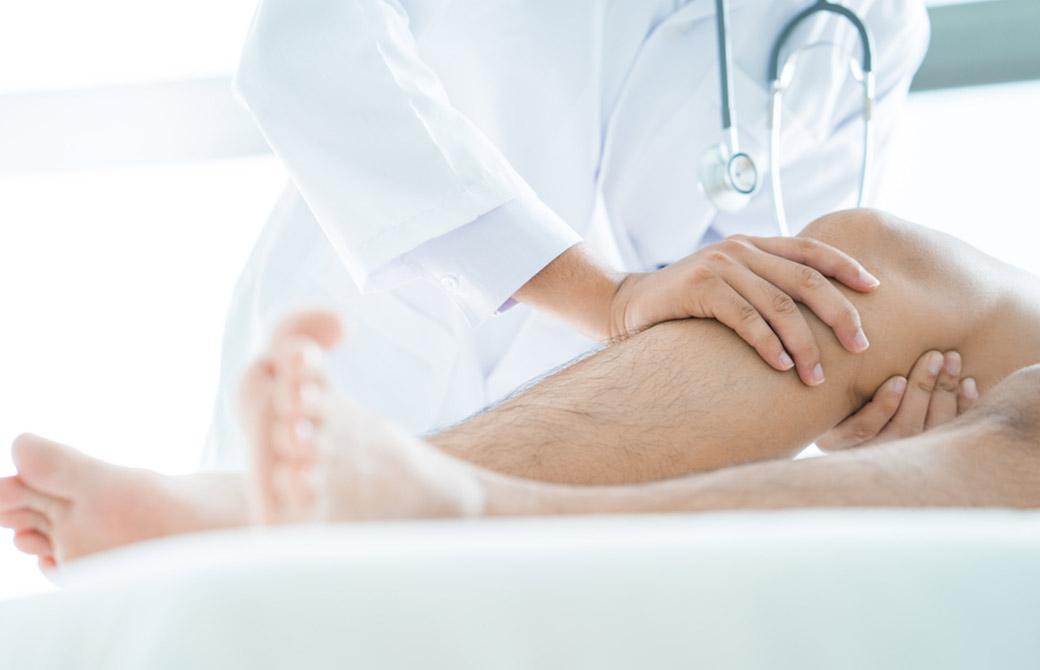 お医者さんが膝の怪我を診ている