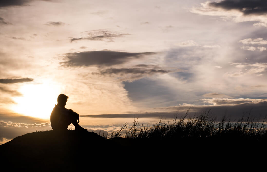 岸辺にたたずみ海を眺める少年