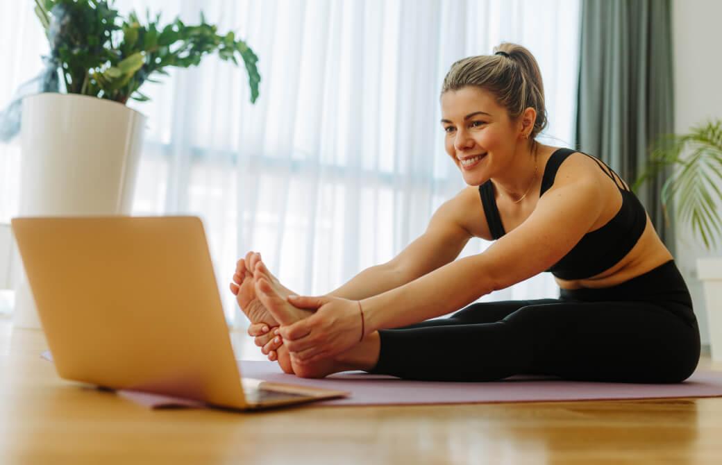 パソコンの画面を見ながらヨガをする女性