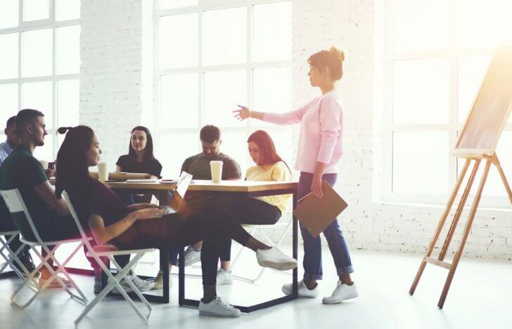 白く明るい部屋でミーティングをしている男女