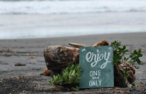 今井浜にenjoyONEandONLYと書かれた黒板が置かれている