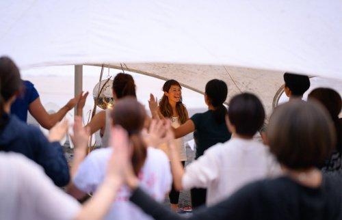 テントの下、たくさんの参加者の前で笑顔でインストラクションをするマイコ先生