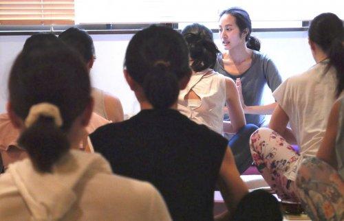 大勢の生徒さんの前でヨガを指導するサントーシマ香