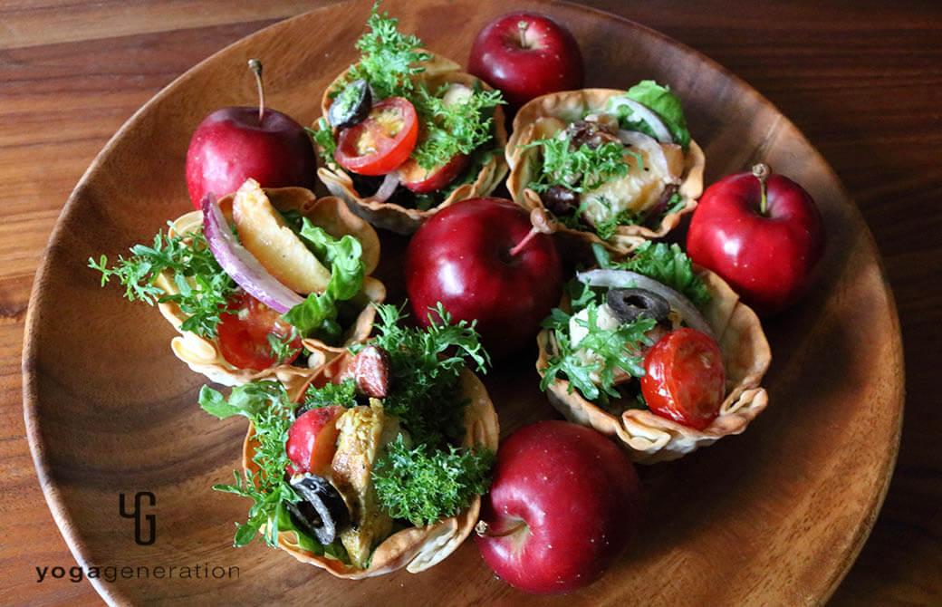 餃子の皮の器に盛りつけたスパイシーチキンとフレッシュなリンゴのサラダ