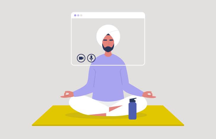 座っているインド人のヨガの先生とPC画面