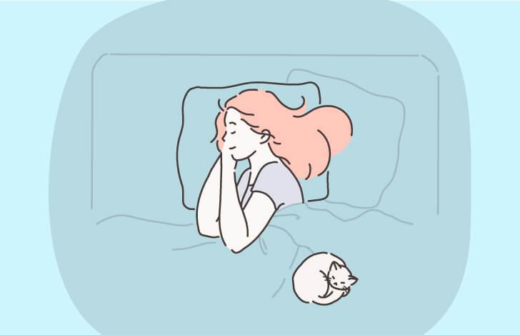 ベッドで眠る女性と猫