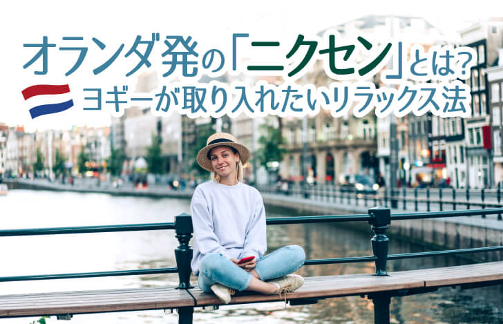 街の中を流れる川沿いに座る女性
