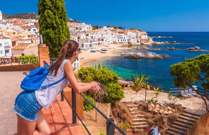 海を眺める女性とヨーロッパの街並み