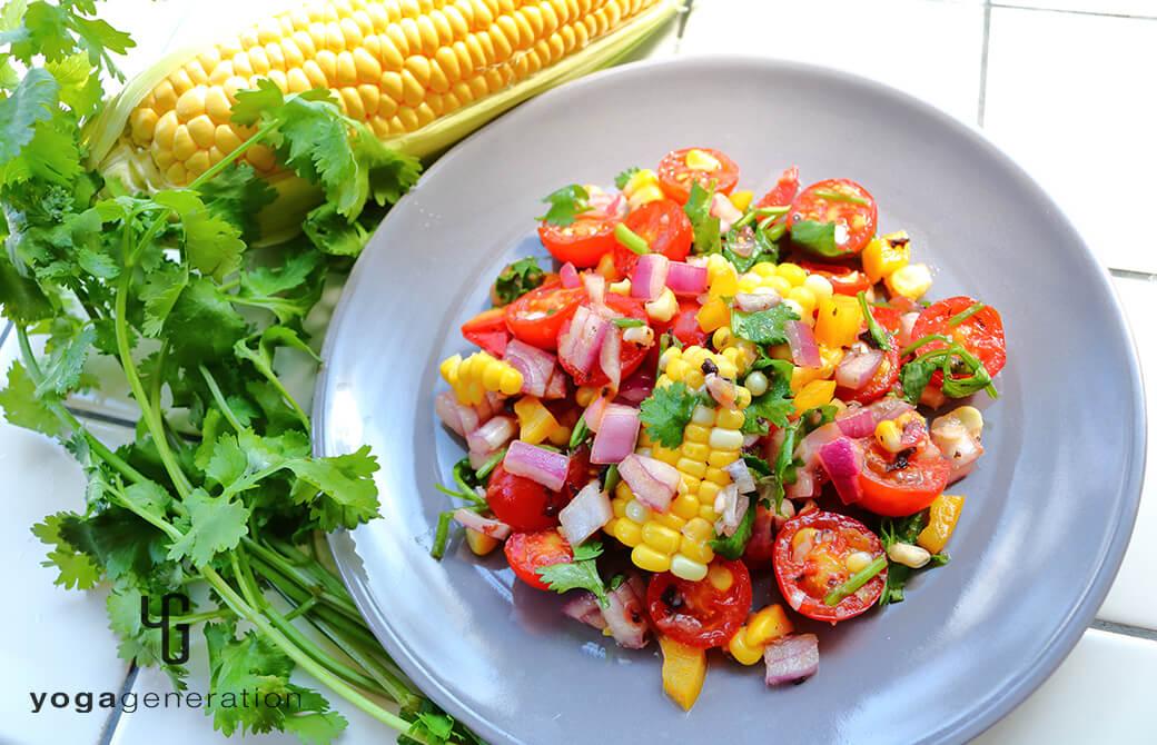 グレーのお皿に盛りつけたトウモロコシとトマトのザクザク・サラダ