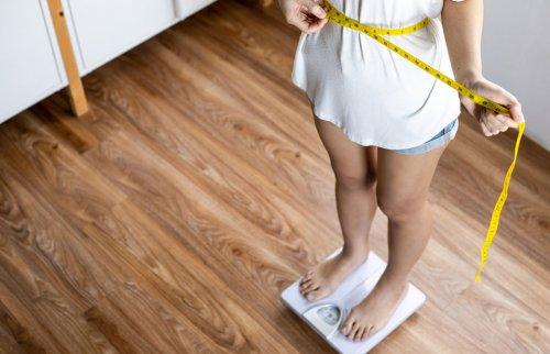 体重計に乗ってウエストを測定する女性