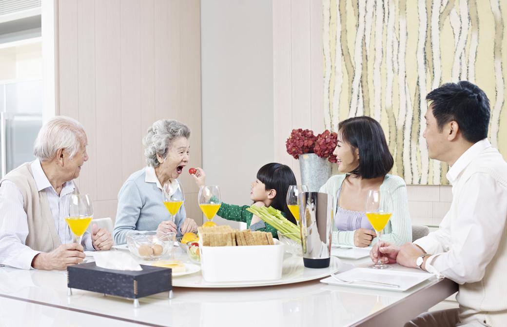 家族3世代が食卓を囲んでいる。おばあちゃんの口に食べ物を運ぶ女の子の孫