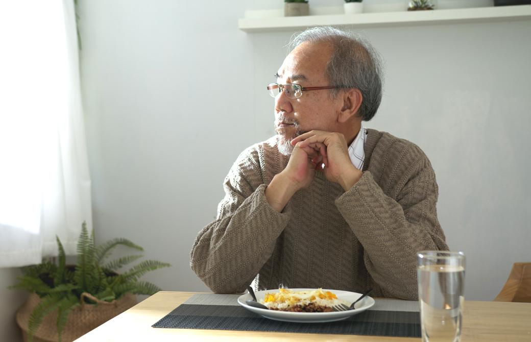 1人で食事をしている老齢の男性