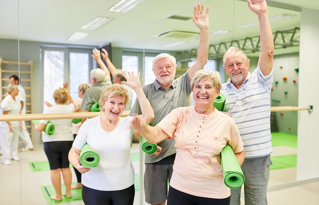 スポーツクラブでヨガマットを持って手を振る老人の男女