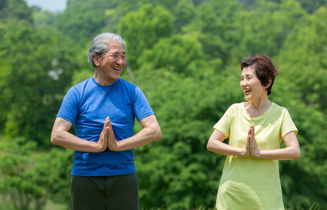 緑の木の前で高齢の男性と女性が合掌をして、目を合わせて微笑んでいる