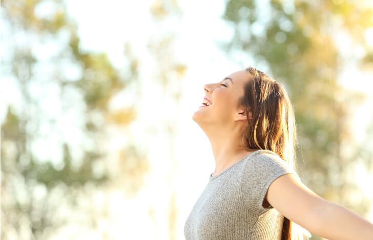 自然の中で深呼吸をする女性