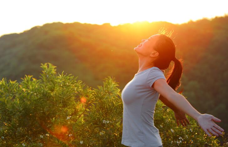 自然の中で両手を広げて深呼吸する女性