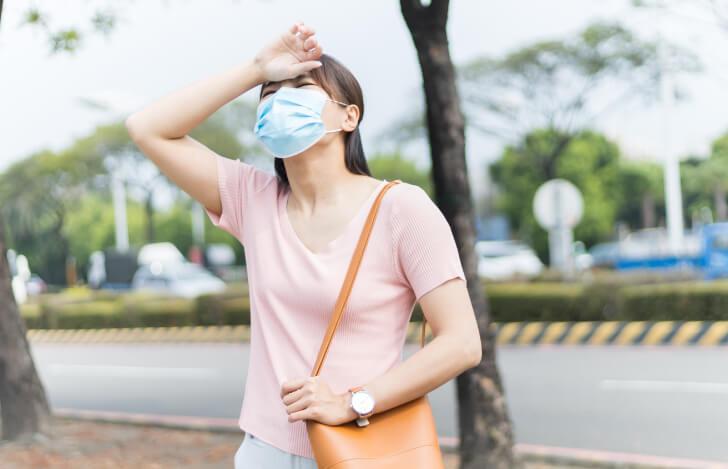 熱中症で額に手を当てるマスク姿の女性