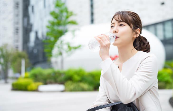 屋外で座って水を飲む女性