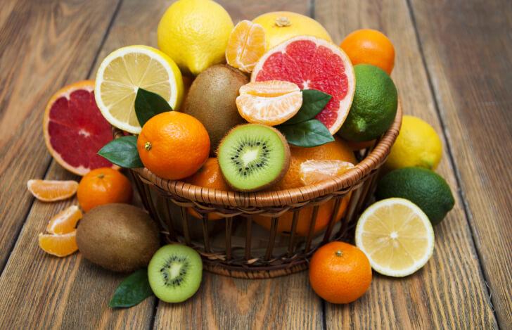 カゴに盛られた柑橘系の果物とキウイ