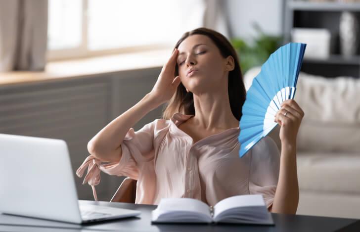 パソコンに向かいながら扇子で仰ぐ疲れた女性