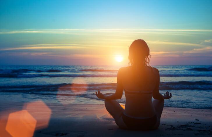 砂浜で夕焼けを眺める女性の後ろ姿