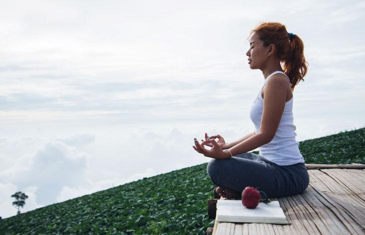 ヨガの本を傍に瞑想する女性