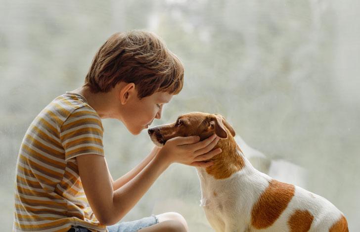 犬にキスをする少年