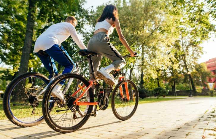 サイクリングをしている男女の後ろ姿
